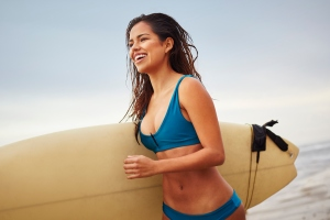 Young woman running on beach carrying surfboard, San Diego, California, USA