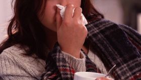 Woman blowing nose on couch with cup of tea