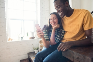 Happy young couple sitting on stairs in a loft sharing cell phone