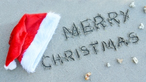 Words ''Merry Christmas'' written on sand at the beach and santa Hat