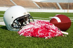American football, helmet, and pom poms on field in stadium.