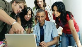 Group of young people gathered around laptop computer